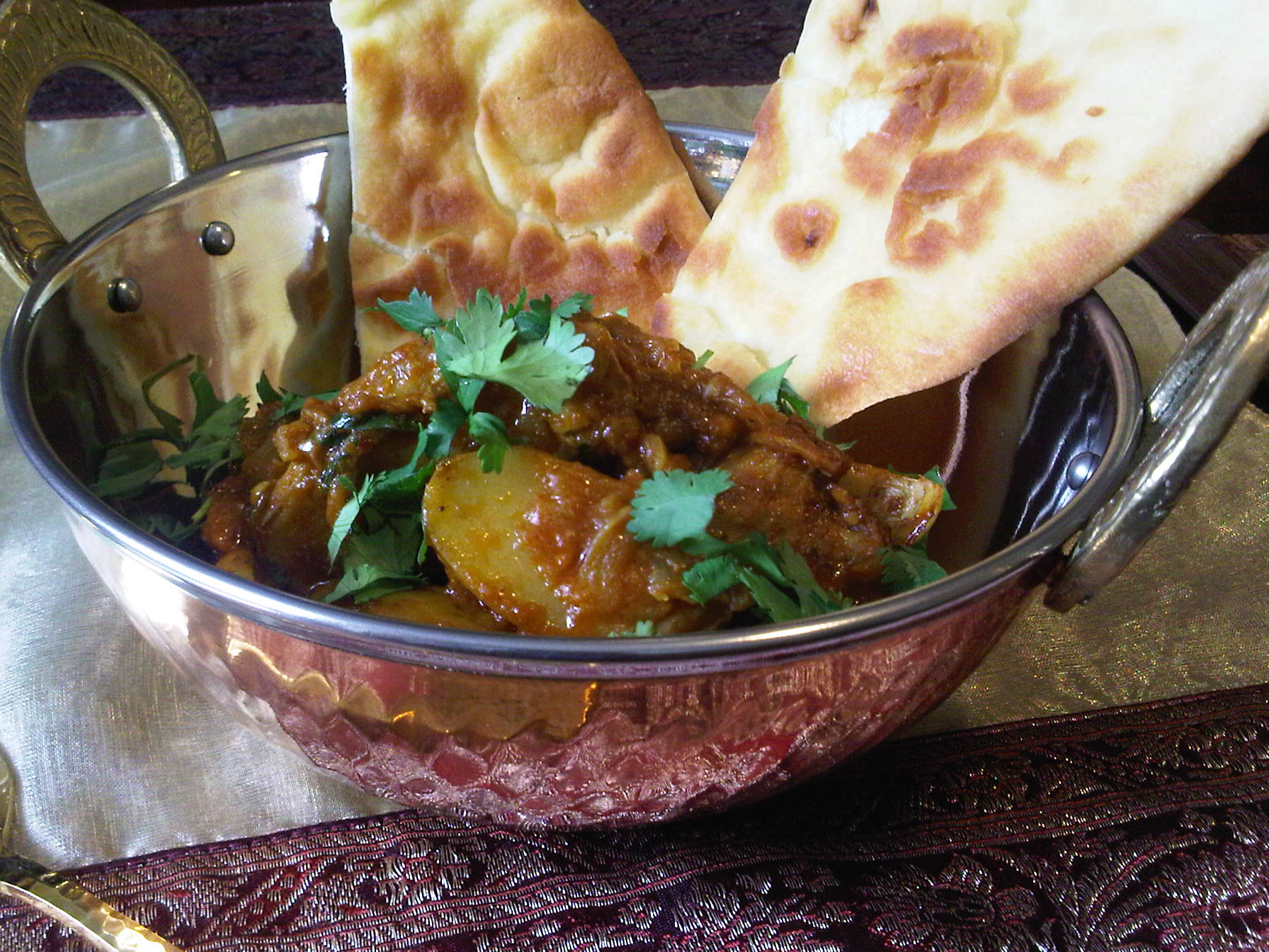 Chicken Curry in copper bowl with naan