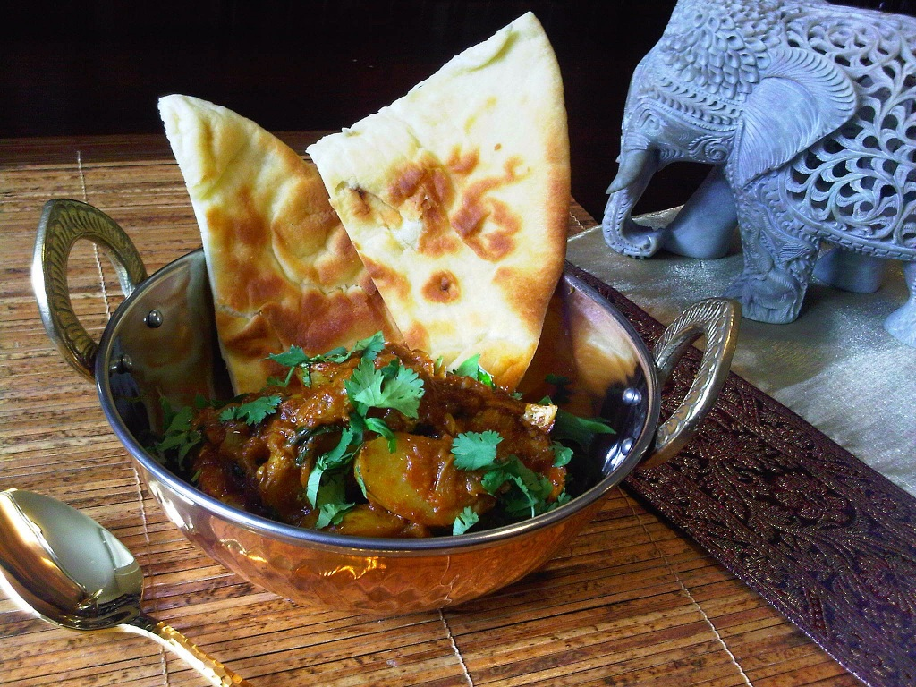 Indian Chicken Curry in copper bowl with naan