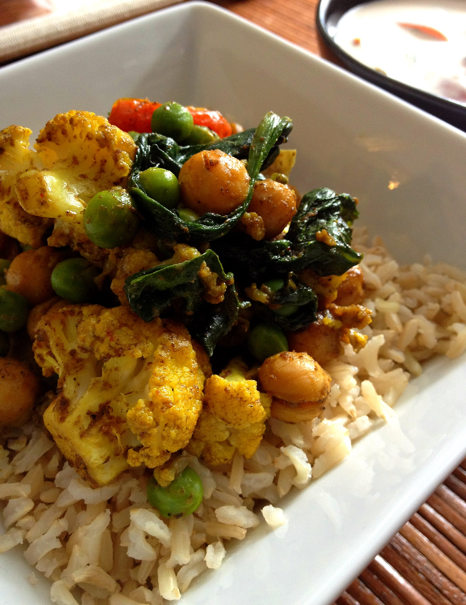 Indian Rice Bowl: oven-roasted curried cauliflower, tomatoes, chick peas, baby spinach, and green peas over steamed brown basmati rice